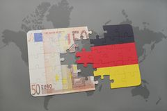 Puzzle with the national flag of germany and euro banknote on a world map background. Stock Photo