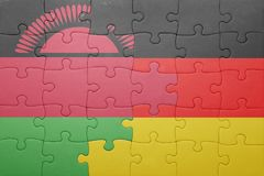 Puzzle with the national flag of germany and malawi. Concept Royalty Free Stock Photos