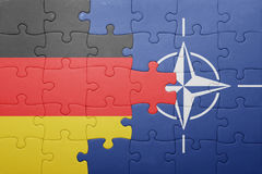 Puzzle with the national flag of germany and nato. Concept royalty free stock images