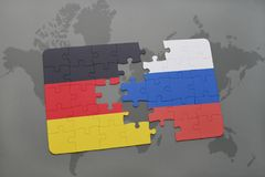 Puzzle with the national flag of germany and russia on a world map background. 3D illustration Royalty Free Stock Image