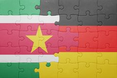 Puzzle with the national flag of germany and suriname. Concept Stock Photos