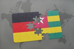 Puzzle with the national flag of germany and togo on a world map background. 3D illustration royalty free stock image