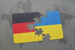 Puzzle with the national flag of germany and ukraine on a world map background. 3D illustration royalty free stock image
