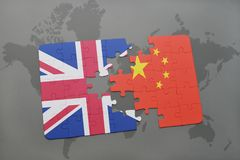 Puzzle with the national flag of great britain and china on a world map background. Concept Stock Image