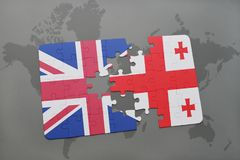 Puzzle with the national flag of great britain and georgia on a world map background. Concept Royalty Free Stock Photo