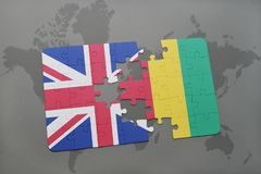 Puzzle with the national flag of great britain and guinea on a world map background. Stock Image