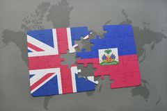 Puzzle with the national flag of great britain and haiti on a world map background. Stock Image