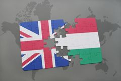 Puzzle with the national flag of great britain and hungary on a world map background Stock Images