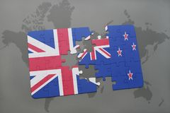 Puzzle with the national flag of great britain and new zealand on a world map background. Concept Stock Photography