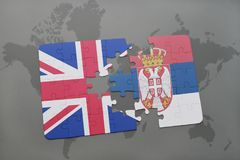 Puzzle with the national flag of great britain and serbia on a world map background. Concept Stock Photo