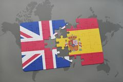 puzzle with the national flag of great britain and spain on a world map background Stock Images
