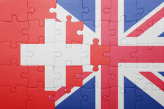 Puzzle with the national flag of great britain and switzerland. Concept Stock Photos