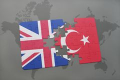 Puzzle with the national flag of great britain and turkey on a world map background Stock Photo