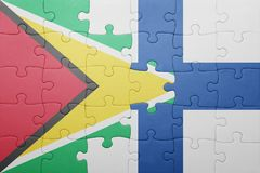Puzzle with the national flag of guyana and finland. Concept Royalty Free Stock Images