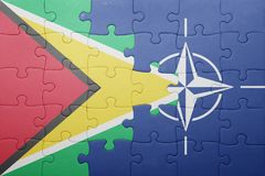 Puzzle with the national flag of guyana and nato Royalty Free Stock Photography