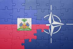 Puzzle with the national flag of haiti and nato. Concept stock photo