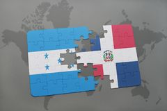 puzzle with the national flag of honduras and dominican republic on a world map background. Royalty Free Stock Image