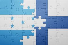 Puzzle with the national flag of honduras and finland. Concept Royalty Free Stock Images