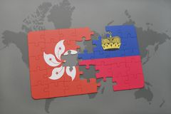 Puzzle with the national flag of hong kong and liechtenstein on a world map background. Royalty Free Stock Photography