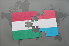 Puzzle with the national flag of hungary and luxembourg on a world map background. 3D illustration Stock Photos