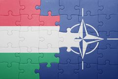 Puzzle with the national flag of hungary and nato. Concept royalty free stock images