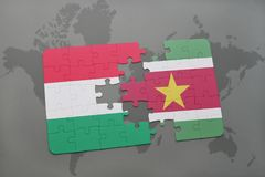 Puzzle with the national flag of hungary and suriname on a world map Stock Photos