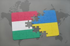 Puzzle with the national flag of hungary and ukraine on a world map background. Stock Images