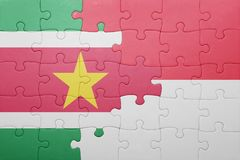 Puzzle with the national flag of indonesia and suriname. Concept Royalty Free Stock Photo