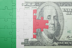 Puzzle with the national flag of italy and dollar banknote. Concept Stock Images