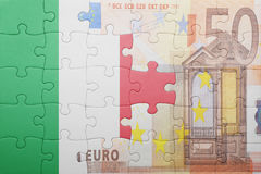 Puzzle with the national flag of italy and euro banknote stock photography