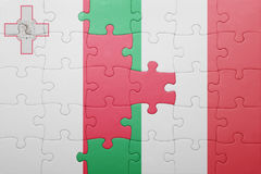 Puzzle with the national flag of italy and malta. Concept Royalty Free Stock Photography