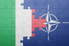 Puzzle with the national flag of italy and nato. Concept stock photo