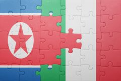 Puzzle with the national flag of italy and north korea Royalty Free Stock Photo