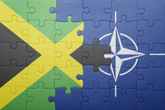 Puzzle with the national flag of jamaica and nato. Concept stock photo