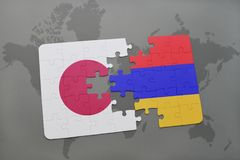 Puzzle with the national flag of japan and armenia on a world map background. Stock Images