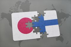 Puzzle with the national flag of japan and finland on a world map background. Royalty Free Stock Photography