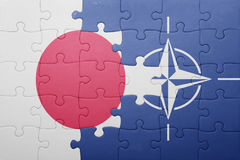 Puzzle with the national flag of japan and nato Stock Image