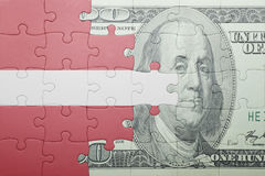 Puzzle with the national flag of latvia and dollar banknote Royalty Free Stock Photo