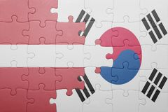 Puzzle with the national flag of latvia and south korea. Concept royalty free stock photo