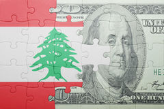 Puzzle with the national flag of lebanon and dollar banknote. Concept stock photo