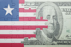 Puzzle with the national flag of liberia and dollar banknote. Concept Royalty Free Stock Photos