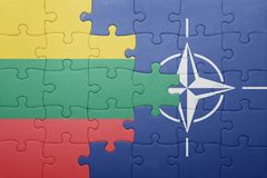Puzzle with the national flag of lithuania and nato. Concept royalty free stock photo