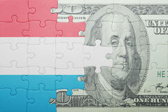 Puzzle with the national flag of luxembourg and dollar banknote. Concept Stock Photos