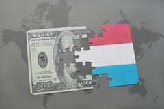 Puzzle with the national flag of luxembourg and dollar banknote on a world map background. 3D illustration Stock Photography