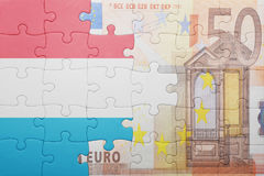 Puzzle with the national flag of luxembourg and euro banknote. Concept Stock Images