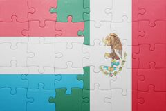 Puzzle with the national flag of luxembourg and mexico. Concept stock photo