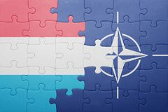 Puzzle with the national flag of luxembourg and nato. Concept royalty free stock images