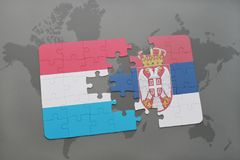 Puzzle with the national flag of luxembourg and serbia on a world map background. 3D illustration Stock Image