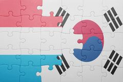 Puzzle with the national flag of luxembourg and south korea. Concept royalty free stock images
