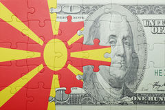 Puzzle with the national flag of macedonia and dollar banknote Stock Images
